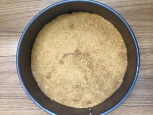 Graham cracker crumb mixture pressed into springform pan and ready for baking.