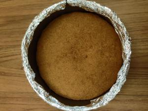 Graham cracker crust baked and out of the oven - pan wrapped with aluminum foil to ensure no leaks during water bath baking of the cheesecake.